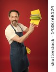 Small photo of For dusting surfaces. Mature man holding cleaning cloths of assorted colors. Eldery housekeeper presenting cleaning towels. Senior man in apron with rubber gloves. Household worker. Household service.