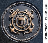 Small photo of Los Angeles, California USA - March 12 2019: U.S. Coast Guard emblem, crest or plaque on black granite background