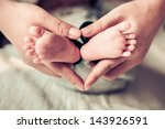 newborn baby feet on female... | Shutterstock . vector #143926591