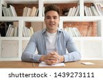Small photo of Serious millennial male coach or speaker sit at desk record online training or study course, focused young tutor talk with viewers shoot live tutorial, make video broadcast with internet subscribers