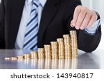 Small photo of Close-up Of Businessman Hand Put Coins To Stack Of Coins