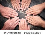 Small photo of group of hands touch each other like a seance. Caucasian people women and men. Dark wooden table on background