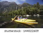 Three Young People Kayaking In...