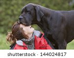 Stock photo girl laughing while her dog kisses tender moment 144024817