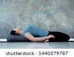 Cauacasian woman resting in reclining hero pose or Supta Virasana with bolster, stretching after practice. Studio shot