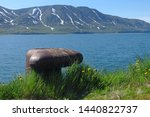 Old metal rusty mooring bollard with a chain wrapped around with the mountain landscsape on background
