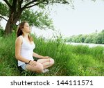 woman meditating in the lotus on the River - stock photo