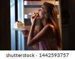 Small photo of Hungry woman in pajamas eating sweet cakes at night near refrigerator. Stop diet and gain extra pounds due to high carbs food and unhealthy night eating