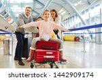 Small photo of Girl spreads her arms and sits on suitcases before departing at the airport terminal