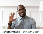 Small photo of Smiling african American millennial man in glasses look at camera waving saying hello talking on video call, happy black male vlogger in spectacles greeting with subscribers shooting video blog