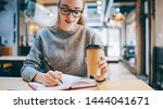 Stock photo intelligent female student in spectacles notes information to textbook while spending time in 1444041671