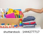 Small photo of Donation concept. Person hand preparing donate box with books, pencils and school supplies for donation