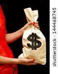 A professional woman presents a cashbag full of money. - stock photo