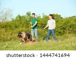 Stock photo young couple walking their dogs in park 1444741694