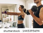 Healthy young couple doing exercises with dumbbells at home. Fit young woman with man doing weights workout indoors in living room. - stock photo