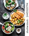 Small photo of Greek style lunch table - baked lemon salmon with potatoes, greek salad, grilled eggplant with tzadziki sauce on dark background, top view. Flat lay