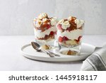 Small photo of Layered dessert Trifle with vanilla cake, whipped cream, salted caramel and fresh strawberry. Two portion in glass on white background. Close up view