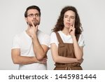 Small photo of Thinking millennial couple pose isolated on grey studio background, pretty girl handsome guy wearing glasses touch chin posture of indecision doubting feelings anxiety, deliberating brain work concept