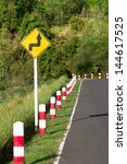 A road sign warns of a sharp turn on a narrow road - stock photo
