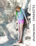 Small photo of woman standing on rocks with acrophobia