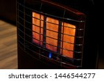 Small photo of An isolated gas heater on a freezing cold winter night burning at full capacity, glowing orange and radiating heat.