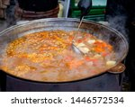cooking in a large cauldron... | Shutterstock . vector #1446572534