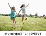 two girls running and jumping... | Shutterstock . vector #144695995