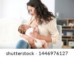 young woman breastfeeding her... | Shutterstock . vector #1446976127