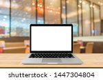 Stock photo blank screen laptop computer on wood table top with blur cafe restaurant with abstract bokeh light 1447304804