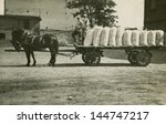 Vintage photo of horse drawn wagon transporting bags, forties - stock photo