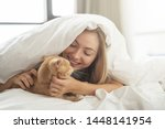 Stock photo cheerful young woman with blonde hair hiding under white blanket with her cat on the bed at home 1448141954