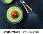 Small photo of Traditional Australian dish called Pie Floater. Green pea soup served with Australian meat pie. Australian cuisine. Black background. Top view. Copy space