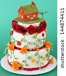 Nice wedding cake with sugar flowers and little house on top