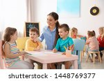Small photo of Little children with kindergarten teacher drawing at table indoors. Learning and playing