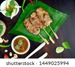Small photo of Pork kicks, grilled pork on banana leaf, grilled with dipping sauce and bread. Grilled skewered milk pork with dipping Sweet mashed bean sauce. Grilled skewer meat or pock are local Thai street food.