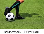 Small photo of soccer ball with foot of player touching it with adumbration