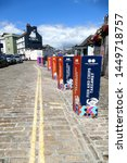 Small photo of Plymouth Devon England. The Barbican July 2019. A surfeit of identical signs placed over bollards advertising fish and chip sales. Differing colour. Cobbled street Parking yellow lines pub in distance