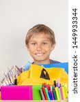 Small photo of Donation concept. Kid holding donate box with books, pencils and school supplies