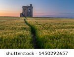 A lookout fort standing proud in a field of wheat at sunset, path in the field leading to the fort nobody in the image