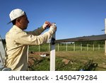 The worker is standing on the ladder and the angular ruler removes measurements of the metal profile of the fence.