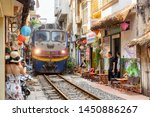 Small photo of Hanoi, Vietnam - April 18, 2019: Incredible view of train passing through a narrow street, the Hanoi Old Quarter. Tourists taking pictures of the train. The Hanoi Train Street is a popular attraction.