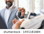 Closeup hand of cardealer giving new car key to customer. Salesman hand giving keys to a client at showroom. Man's hand receiving car keys from african agent in a auto dealership with copy space. - stock photo