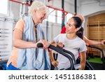 senior woman biking at the gym...   Shutterstock . vector #1451186381