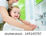 Mother washing kid hands