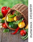 Fresh kitchen garden vegetables with wicker basket. - stock photo