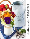 Beautiful colorful Pansies in a creamer and fresh strawberries. - stock photo