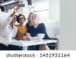 Stock photo group of businesswomen taking selfie at office cafeteria female business professionals taking 1451931164