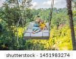 mother and son swinging in the... | Shutterstock . vector #1451983274