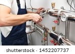 The man is installing the heater system in the house and checking pipes by the wrench - stock photo