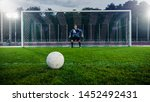 Small photo of Shot of a Football Ball on a Grass during Penalty on Championship. In the Background Professional Goalkeeper Stands in Goals Ready to Defend.